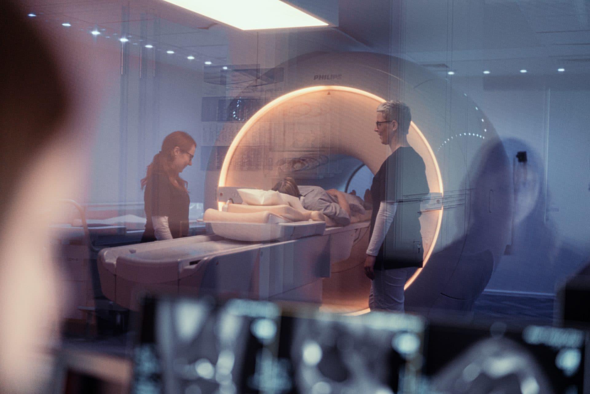 Mitarbeiterinnen fahren Patientin in den 3-Tesla MRT ein