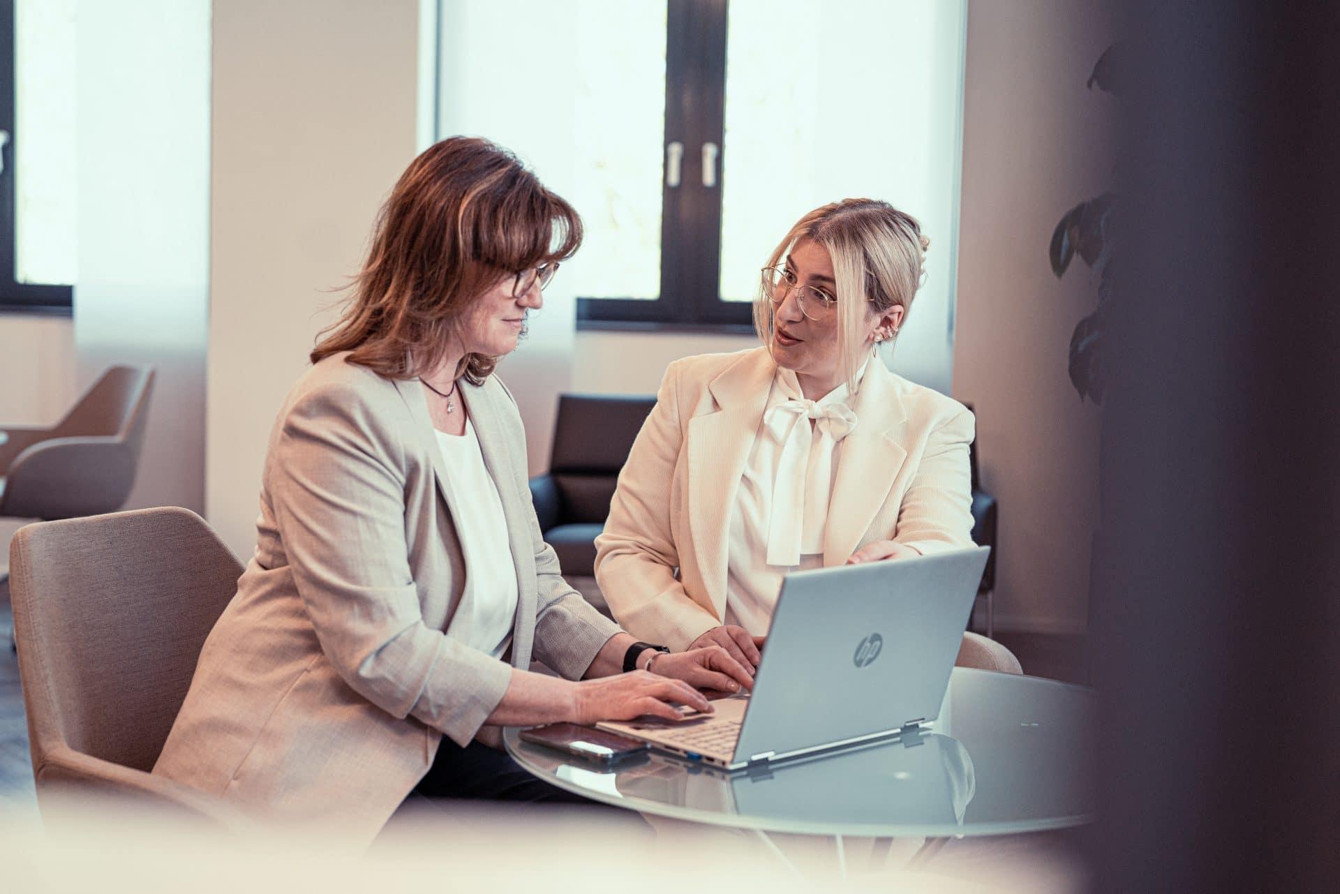 Mitarbeiterinnen besprechen sich gemeinsam am Laptop