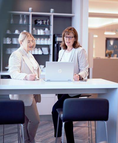 Mitarbeiterinnen unterhalten sich gemeinsam vor einem Laptop und besprechen die Ergebnisse