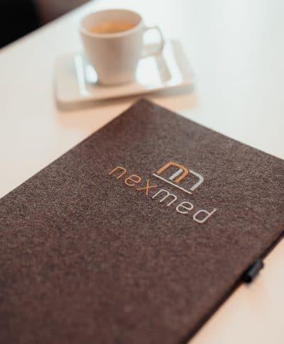 Mit dem nexmed-Logo verzierte Lodenmappe für sämtliche Unterlagen